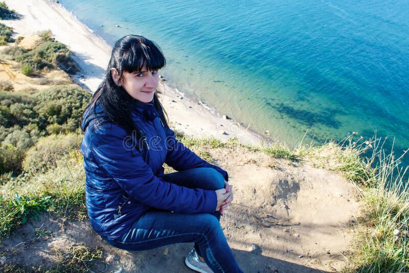 Young woman sitting on a high seashore. Young brunette woman in blue jacket and jeans sitting on a high seashore on sunny autumn day royalty free stock photos