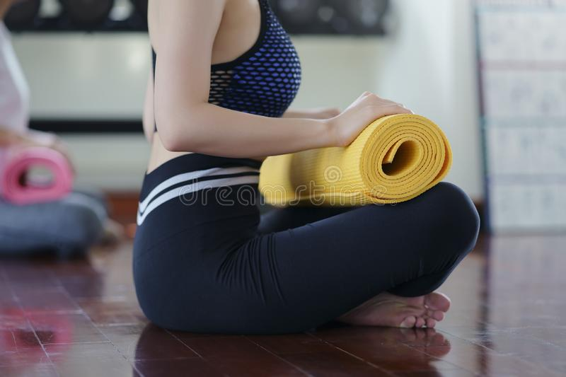 Young woman sitting and holding yoga mat, relaxation after a yoga class at gym. Healthy life concept. stock photo