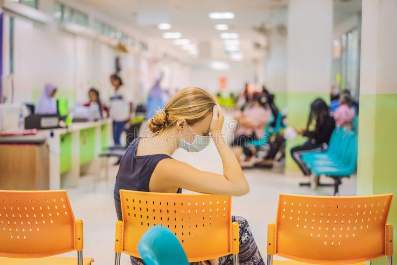 Young woman sitting in hospital waiting for a doctor`s appointment. Patients In Doctors Waiting Room stock image