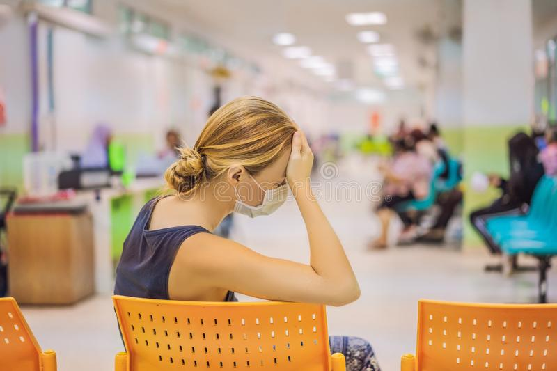 Young woman sitting in hospital waiting for a doctor`s appointment. Patients In Doctors Waiting Room stock images