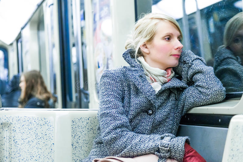 Young Woman Sitting inside a Metro Wagon. Young Woman Using Environmental Public Transportation to go Back Home After Work stock images