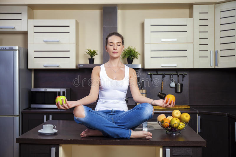 Young woman sitting at the kitchen table in the lotus position. Young beautiful woman sitting at the kitchen table in the lotus position stock photo