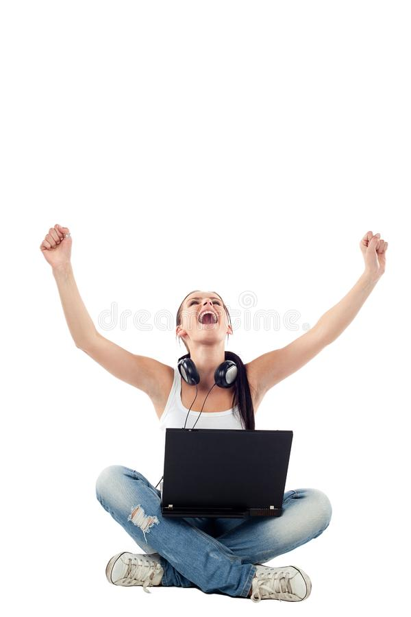 Young woman sitting with laptop raising hands