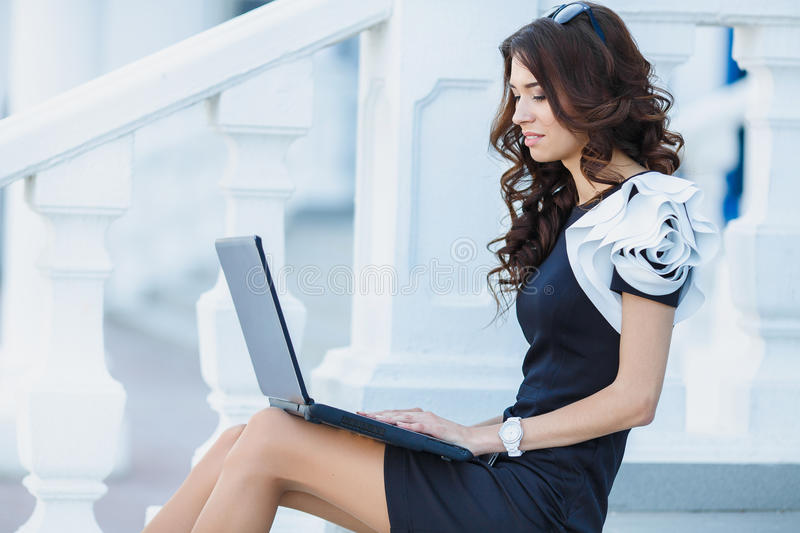 Young woman sitting with a laptop on a summer day stock photo