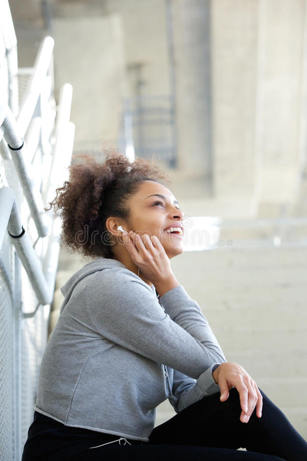 Young woman sitting listening to music with earphones royalty free stock photography