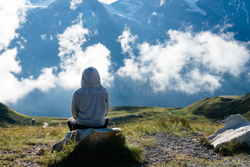 Young woman sitting looking at sea of clouds in mountain landscape royalty free stock images