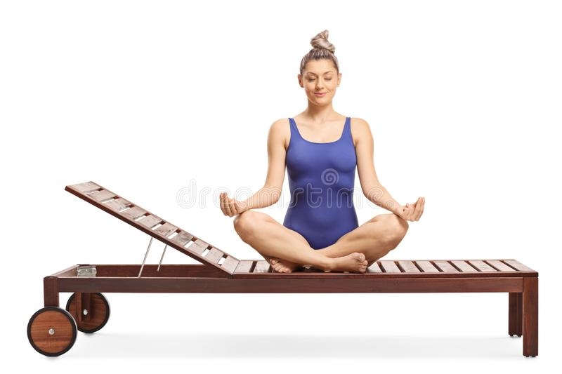 Young woman sitting on a lounge chair practicing meditation stock images