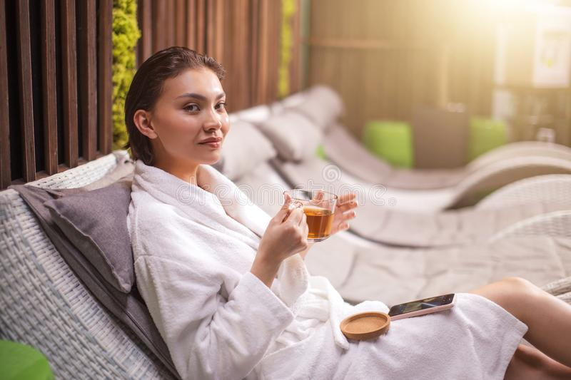 Young woman sitting on the lounge after taking a bath with cup of herbal tea royalty free stock photography