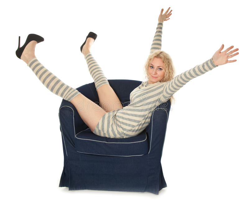 Young woman sitting in a navy armchair stock images