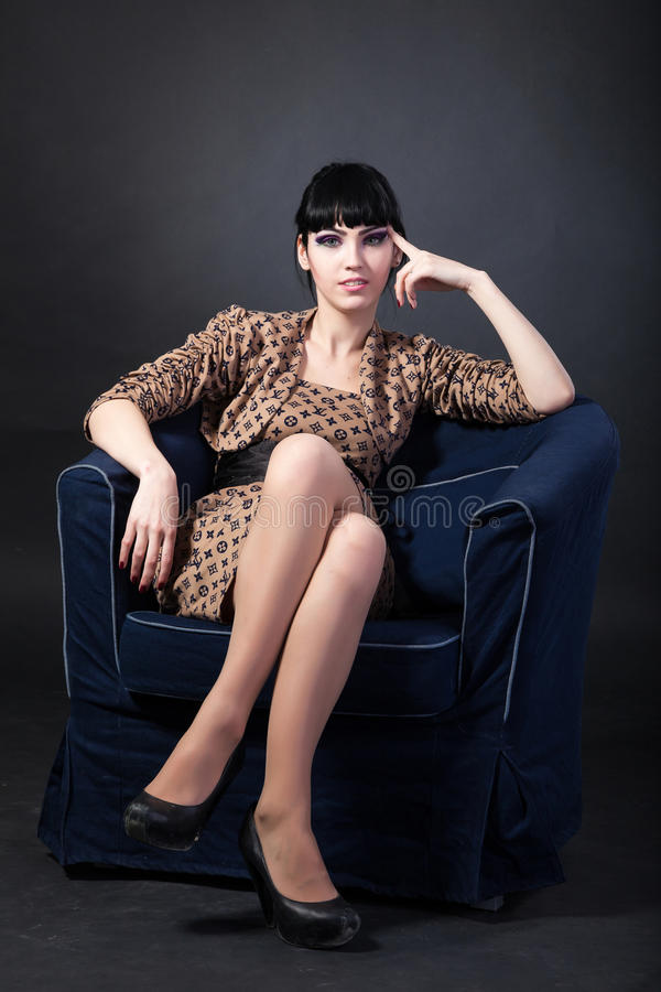 Young woman sitting in a navy armchair royalty free stock photography
