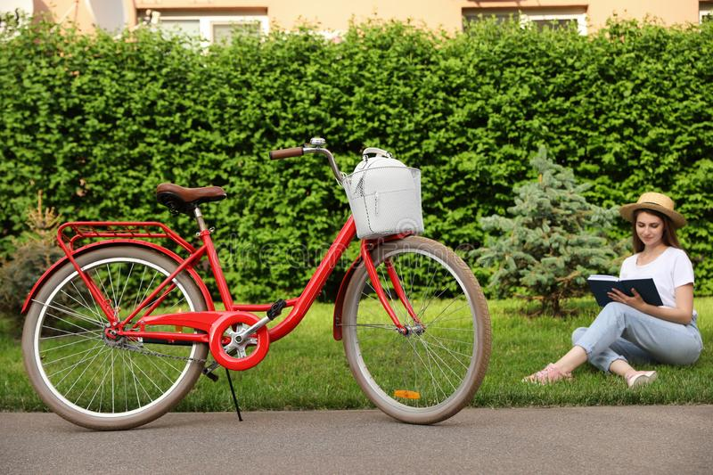 Young woman sitting near modern bicycle on grass. Outside stock image