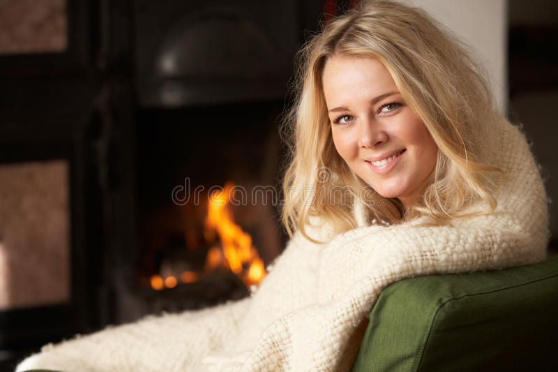 Young woman sitting by open fire. Smiling stock photography
