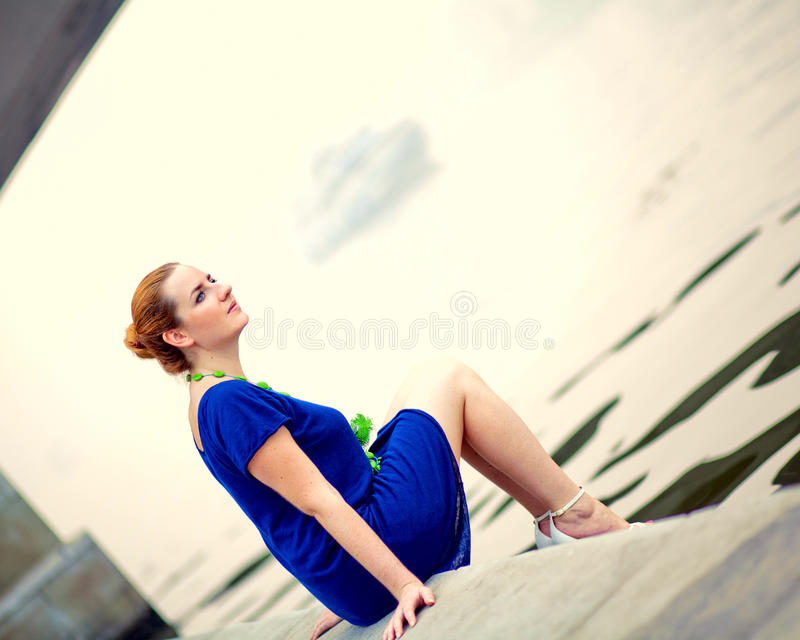 Download Young Woman Sitting On A Pier Stock Image - Image: 27672393