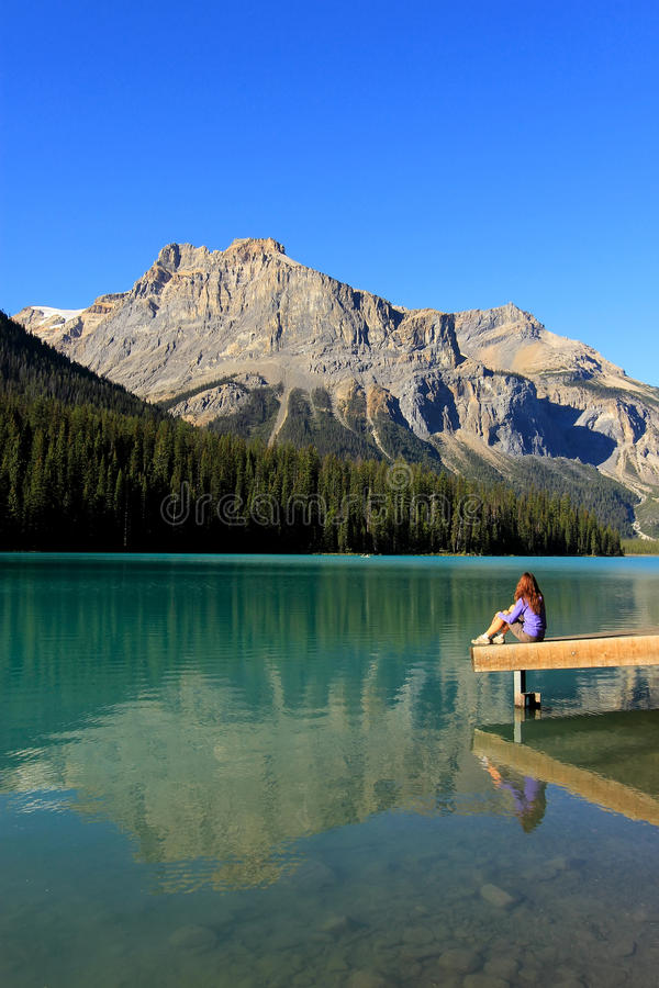 Young woman sitting on a pier at Emerald Lake, Yoho National Par stock image