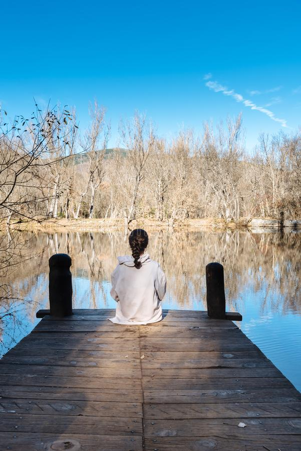 Young woman sitting on pier by the lake stock image