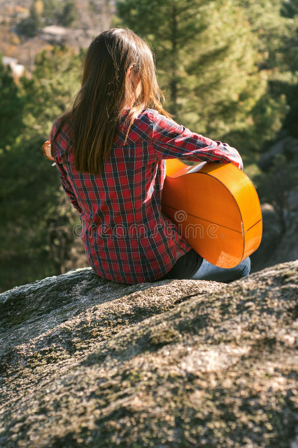Young woman sitting in the pit of the mountains, staring into sp stock photography