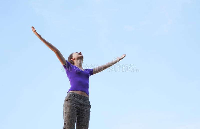 Young Woman Sitting With Raised Hand Stock Photo