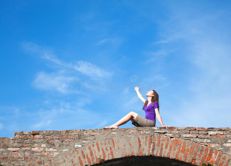 Young Woman Sitting With Raised Hand Stock Photography