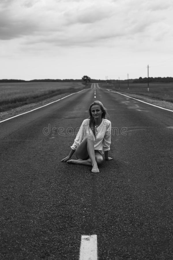 Young woman sitting on a road. Freedom concept. Beautiful young woman sitting on a road. Freedom concept stock photos