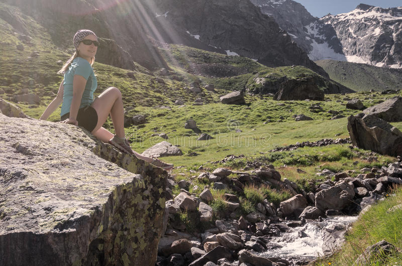 Young woman sitting on a rock at Alps mountains royalty free stock photography