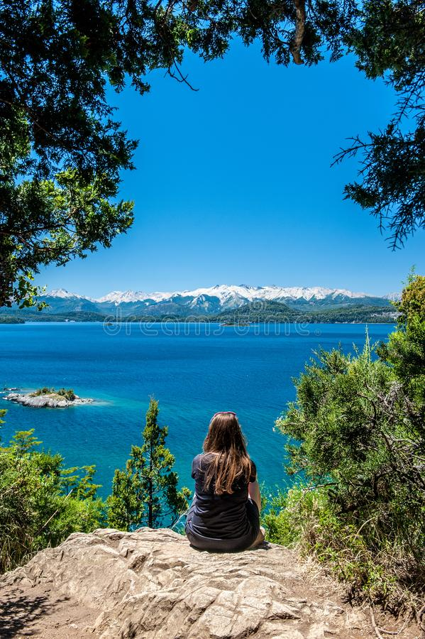Young woman sitting on the rock and watching Nahuel Huapi lake, San Carlos de Bariloche Argentina. Waves on the lake. Mountains. With fresh snow surrounding the stock images