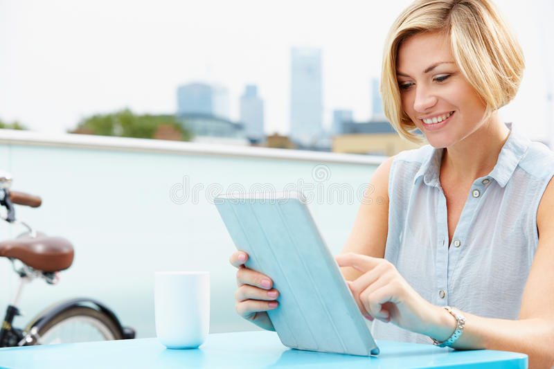 Young Woman Sitting On Roof Terrace Using Digital Tablet Stock Photo