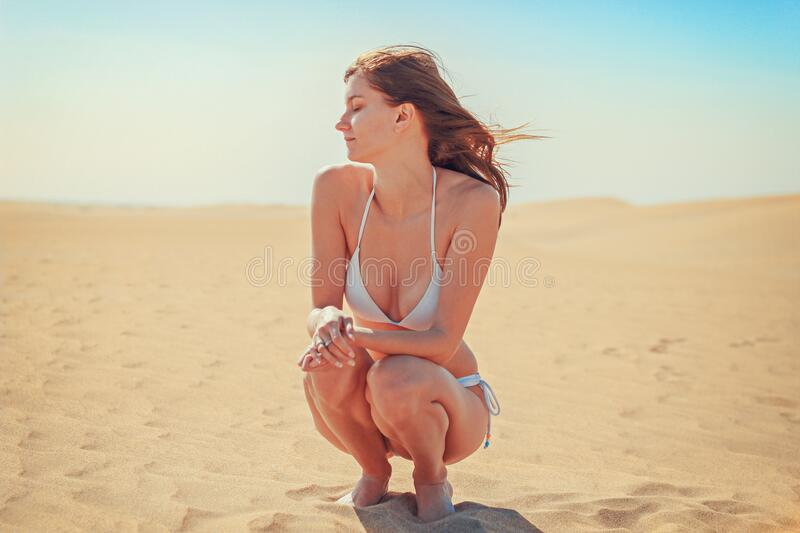 Young Woman Sitting on Sand at Beach stock images