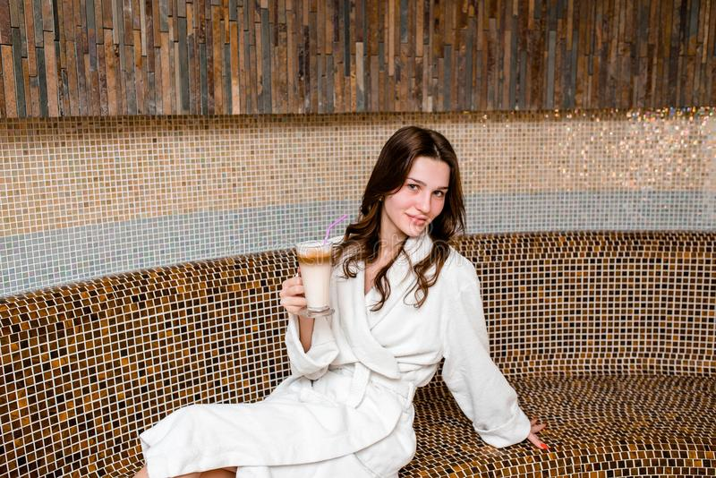 Young woman sitting in sauna and drink coffee.. royalty free stock photos