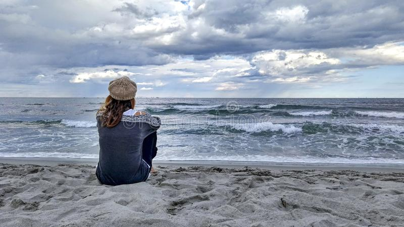 Young woman sitting by the sea with stormy sky, looks at the horizon thoughtfully. Young woman sitting by the sea with stormy sky, looks at the horizon stock image