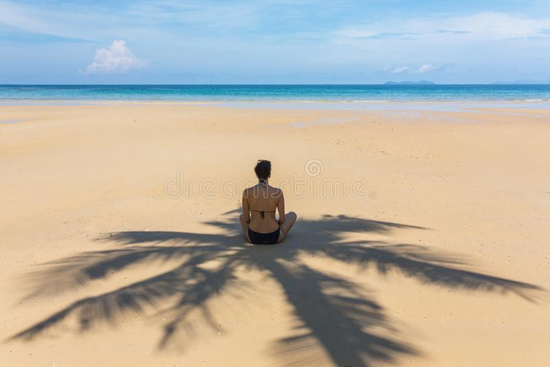 Young woman sitting in the shadow of palm tree on tropical beach royalty free stock photos