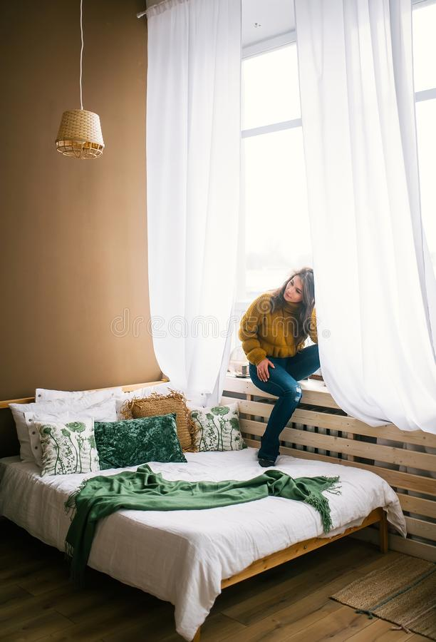 Young woman sitting on sill near big window in bedroom royalty free stock images