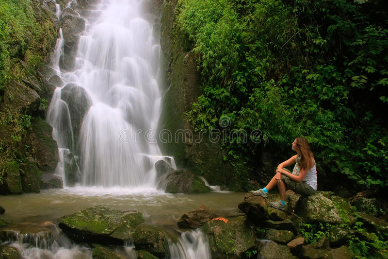 Young woman sitting at Simangande falls on Samosir island, Sumatra, Indonesia. Southeast Asia royalty free stock photography