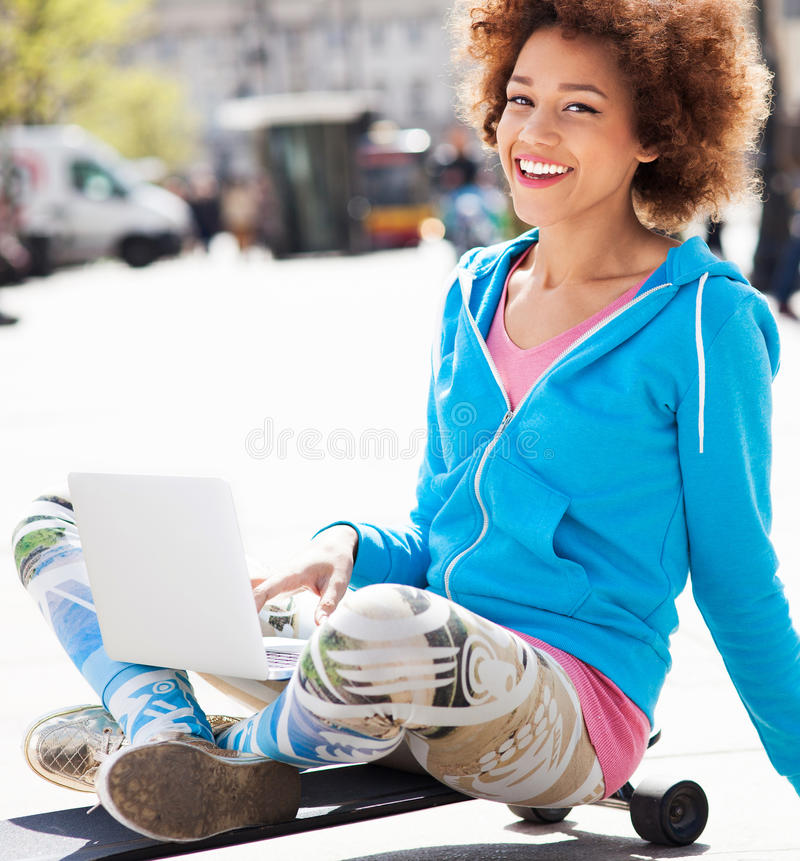Young Woman Sitting On Skateboard With Laptop Stock Photo