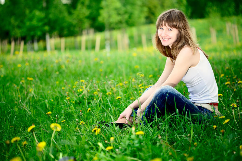 Young woman sitting in spring park stock photography