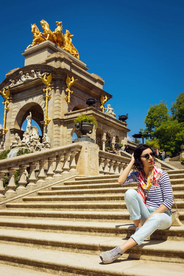 Download Young Woman Sitting On The Staircase In Front Of Fountain Stock Photo - Image: 83723416