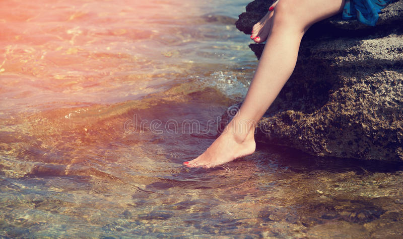 Young woman sitting on a stone, dropped feet into the sea water. stock image