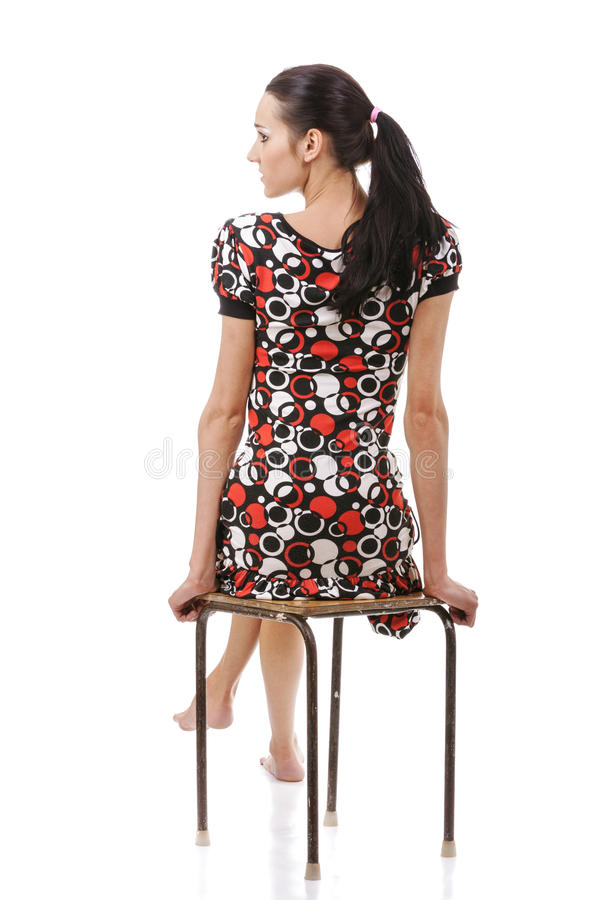 Young woman sitting on stool. Beautiful young woman sitting on stool, isolated on white background royalty free stock photo