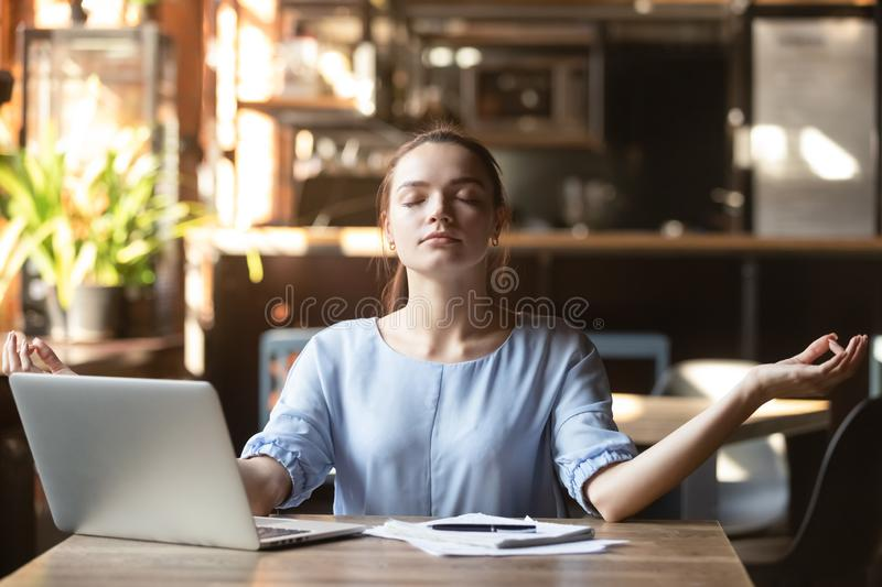 Young woman sitting at table in cafe relaxing do meditation. Young woman sitting in public place take break distracted from work or study do yoga exercise stock photos