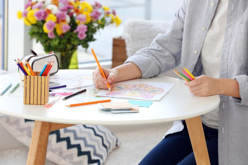 Young woman sitting at table with coloring pictures royalty free stock photo