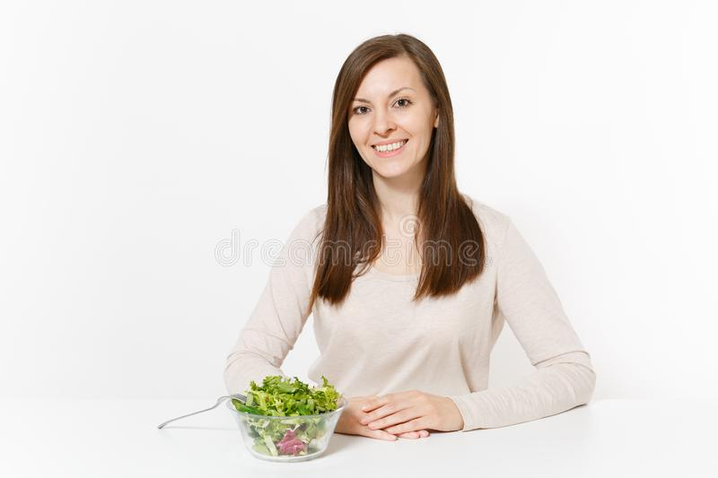 Young woman sitting at table with green leaves salad in glass bowl isolated on white background. Proper nutrition stock images