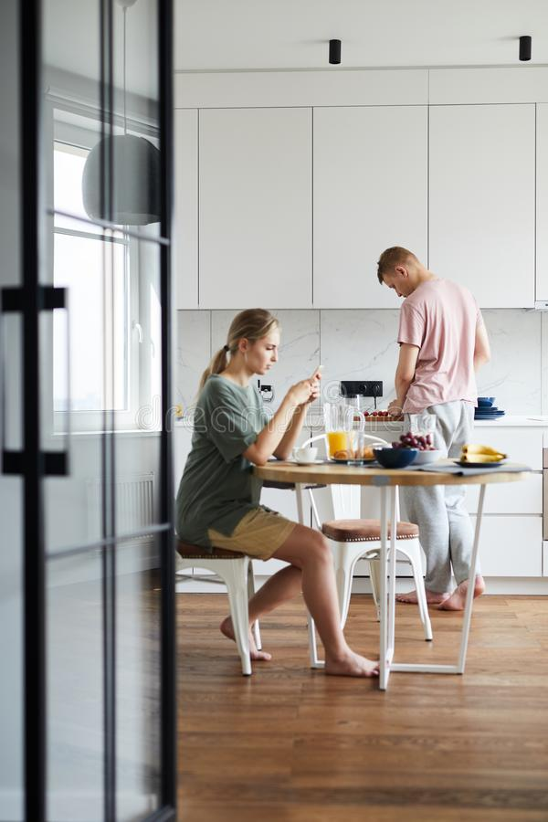 Young woman having breakfast and using smartphone while her husband cooking stock images