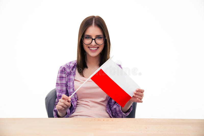 Young woman sitting at the table with Polish flag. Young woman sitting at the table and holding Polish flag over white background and looking at camera royalty free stock photos