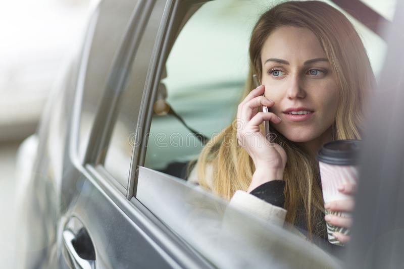 Young woman sitting in a taxi stock images