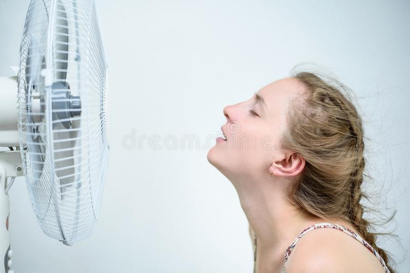 Young woman sitting under a fan with closed eyes from pleasure. Summer heat. White background royalty free stock images