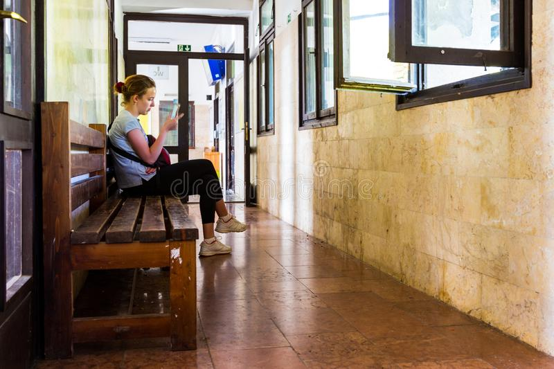 Young woman sitting, using her mobile phone while waiting for the train at retro railway station in Kőszeg, Hungary royalty free stock photography
