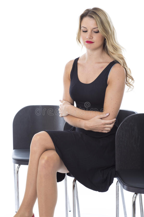 Young Woman Sitting Waiting Arms Folded Looking Down Bored FedUp. Attractive Young Woman Sitting Waiting Arms Folded Looking Down Bored FedUp royalty free stock images