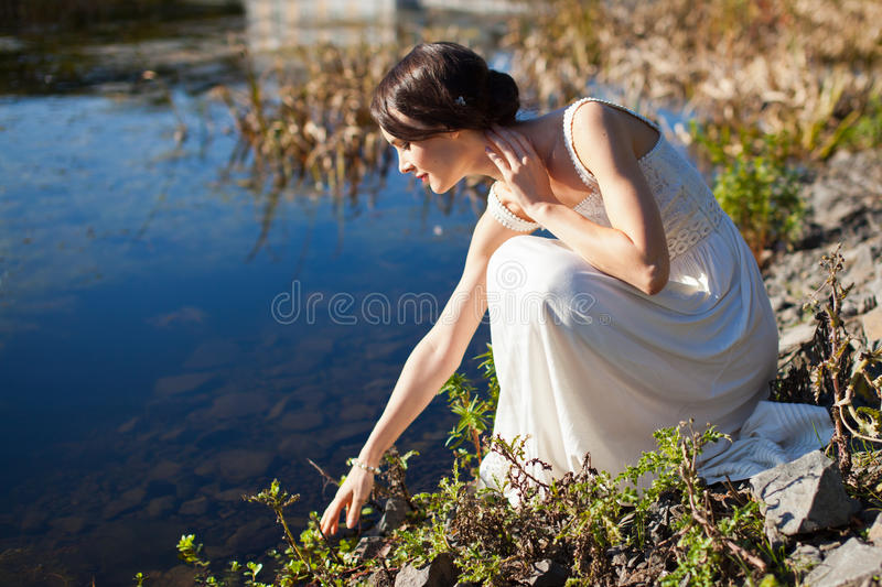 Young woman sitting by water royalty free stock photography