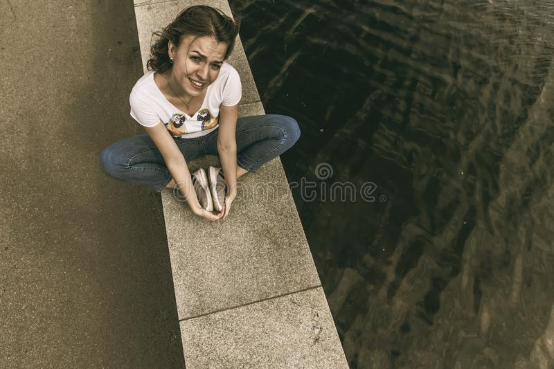 Young woman sitting on the waterfront by the water royalty free stock images
