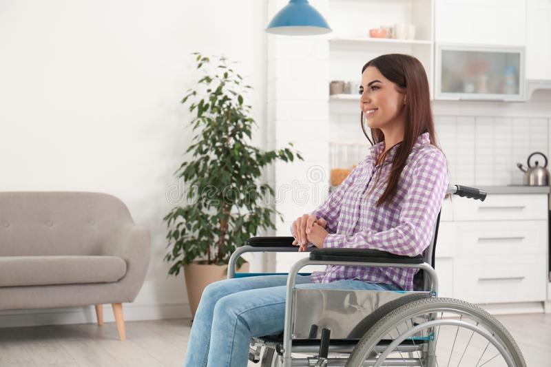 Young woman sitting in  wheelchair indoors royalty free stock images