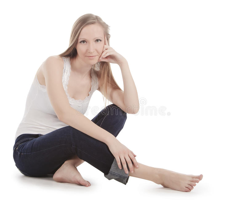 Young woman sitting on a white floor barefoot stock photo